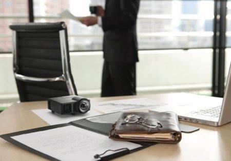 ricoh projecteur press posé sur un bureau. On constate qu'il est aussi grand qu'une paire de lunette